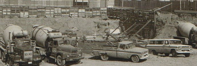Construction trucks and materials in lot circa 1970s